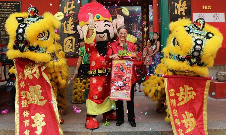 Ambassador Lakhdhir with the God of Prosperity from a lion dance troupe. (U.S. Embassy photo)